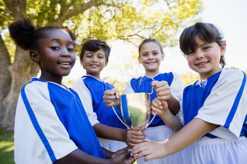 拿着杯子的愉快的儿童足球队员 图库摄影