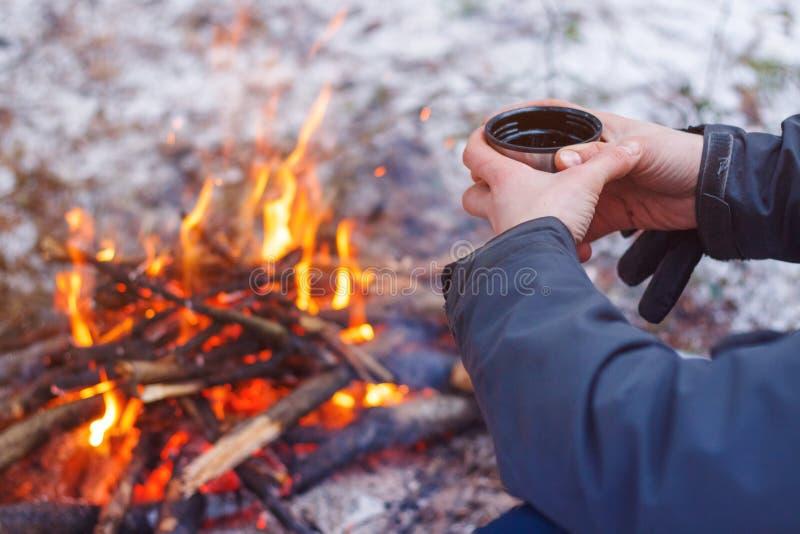 拿着杯子的旅客手在火附近 库存图片