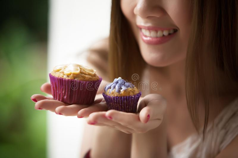 拿着杯子蛋糕的妇女 免版税库存照片