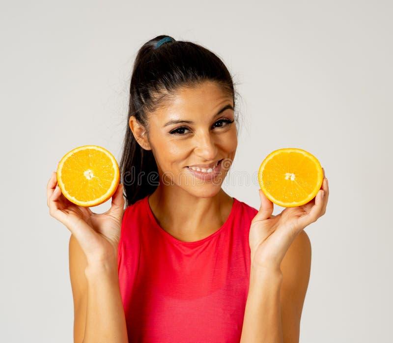 拿着杯新鲜的橙汁和橙色果子的愉快的可爱的运动的妇女 库存照片