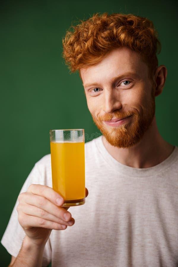 拿着杯桔子的英俊的微笑的有胡子的人画象  免版税库存照片