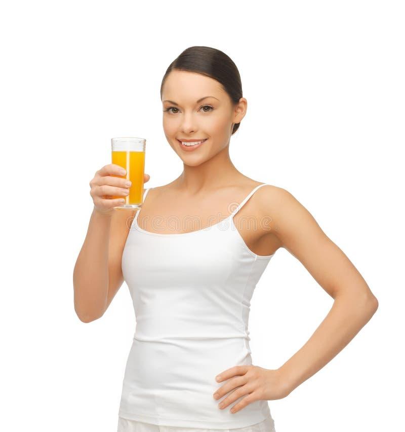 拿着杯橙汁的妇女 图库摄影