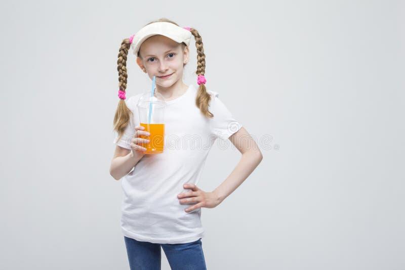 拿着杯汁液的遮阳的微笑的白种人白肤金发的女孩反对白色 免版税库存图片