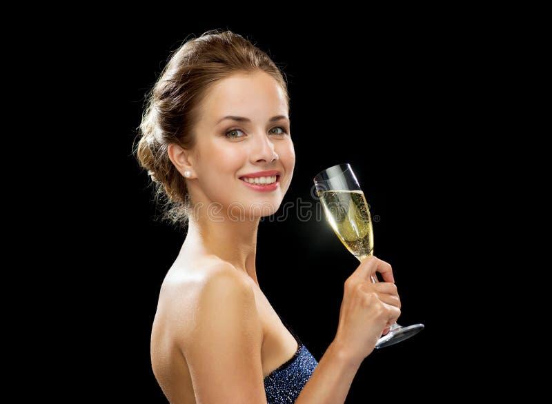 拿着杯汽酒的微笑的妇女 免版税库存照片
