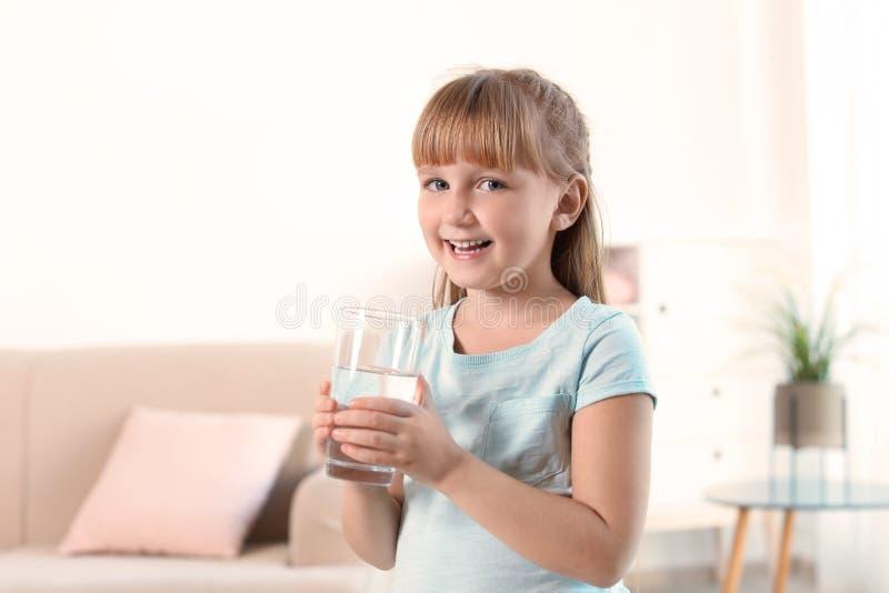 拿着杯淡水的逗人喜爱的小女孩 免版税库存照片