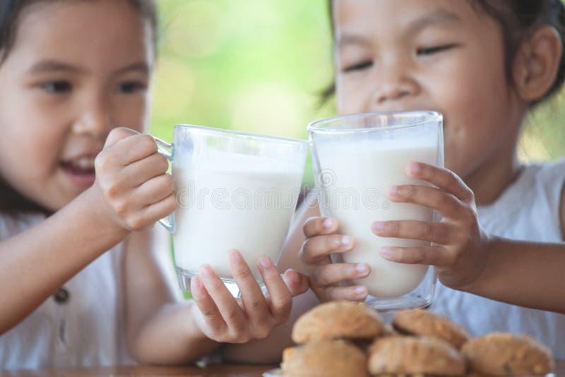 拿着杯牛奶的两个逗人喜爱的亚裔小孩女孩 免版税库存图片