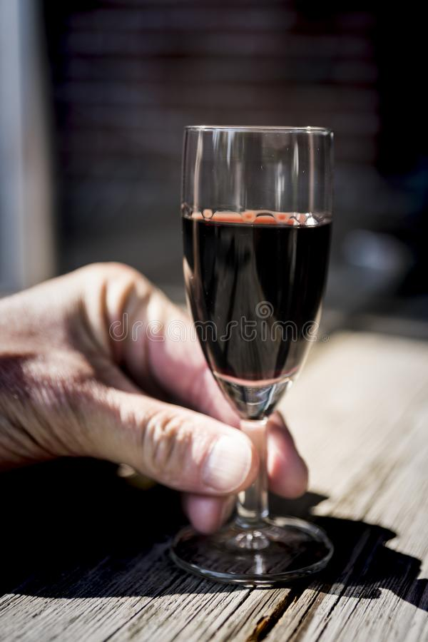 拿着杯红色口岸的手,在木桌上 库存照片