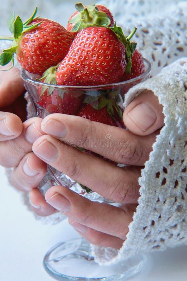 拿着杯草莓的手 图库摄影