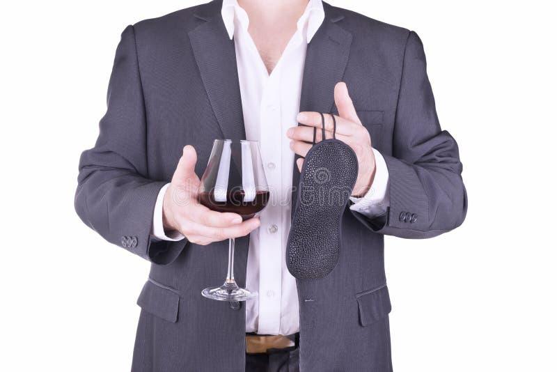 拿着杯酒和眼罩的商人 免版税图库摄影
