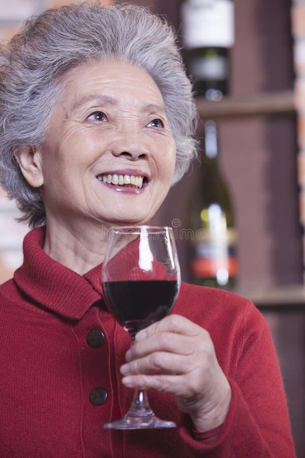 拿着杯酒,画象的红色毛线衣的微笑的资深妇女 图库摄影