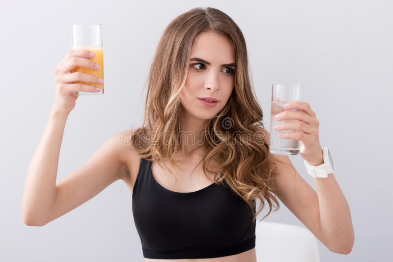 拿着杯水和汁液的宜人的困惑的妇女 免版税库存照片
