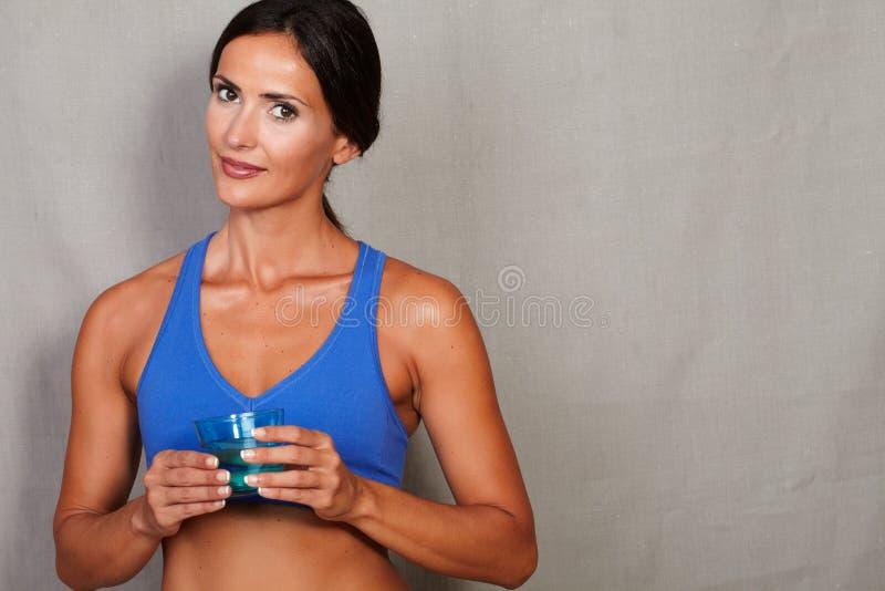 拿着杯水的健康夫人 库存照片