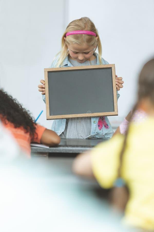 拿着板岩的白种人女小学生在教室在有他的坐在前面的同学的学校 图库摄影