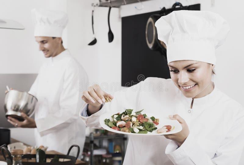 拿着板材的愉快的女性年轻人厨师 免版税库存照片