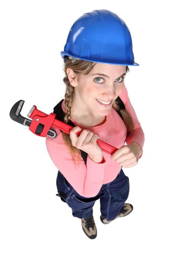 拿着板钳的女性工作者 免版税库存照片
