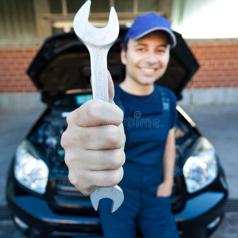 拿着板钳的技工在汽车车库 库存照片