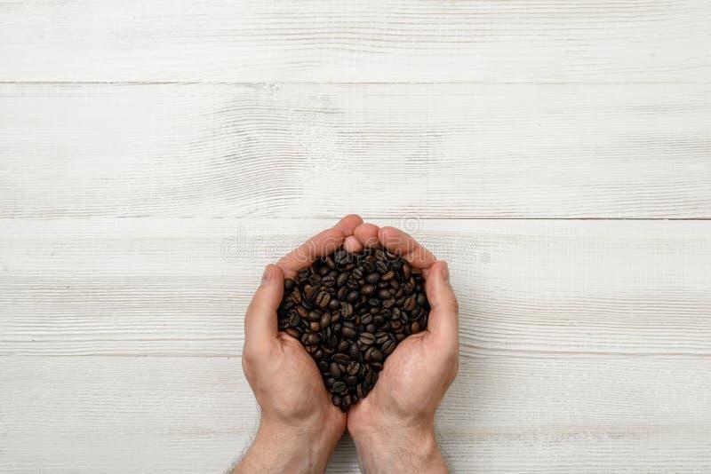 拿着极少数咖啡豆的人的特写镜头手 免版税库存照片