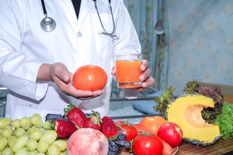 拿着果子健康食物的营养师医生 库存照片