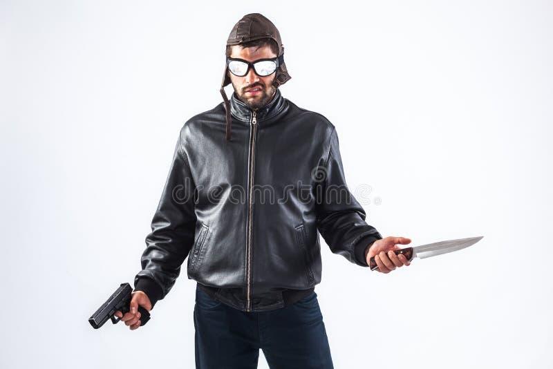 拿着枪和刀子的猛烈年轻人 免版税库存图片