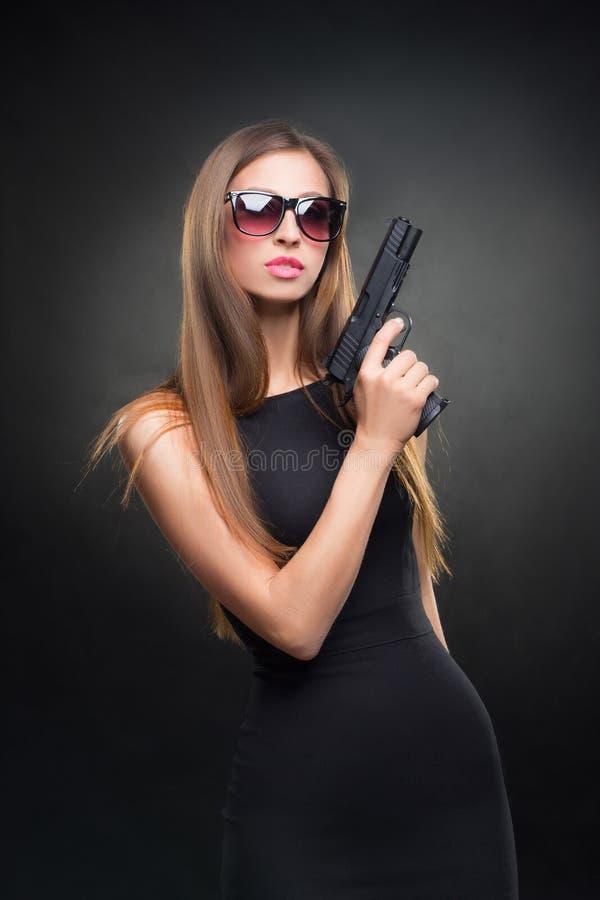 拿着枪的一件黑礼服和太阳镜的女孩 免版税库存照片