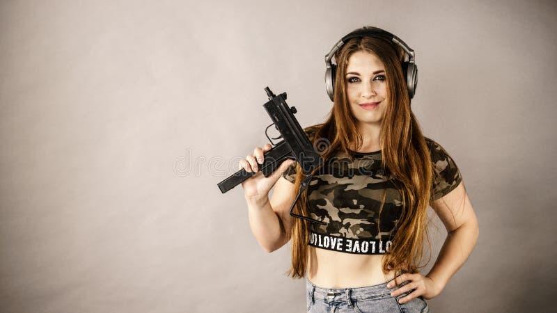 拿着枪的妇女佩带的耳机 库存图片
