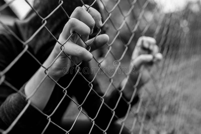 拿着架线的庭院的年轻不可能验明的十几岁的男孩在黑白的修正学院 库存图片