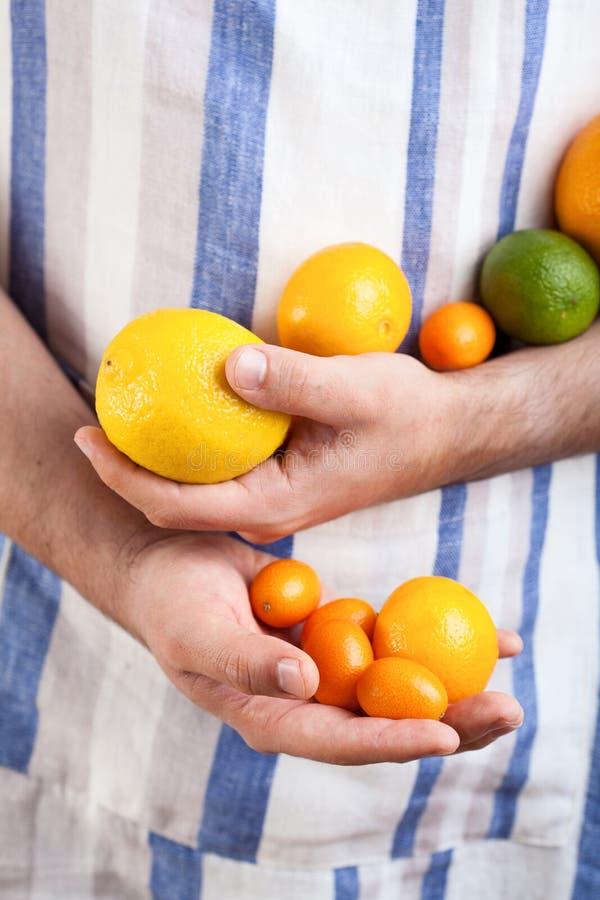 拿着柑橘水果的人手 免版税库存图片