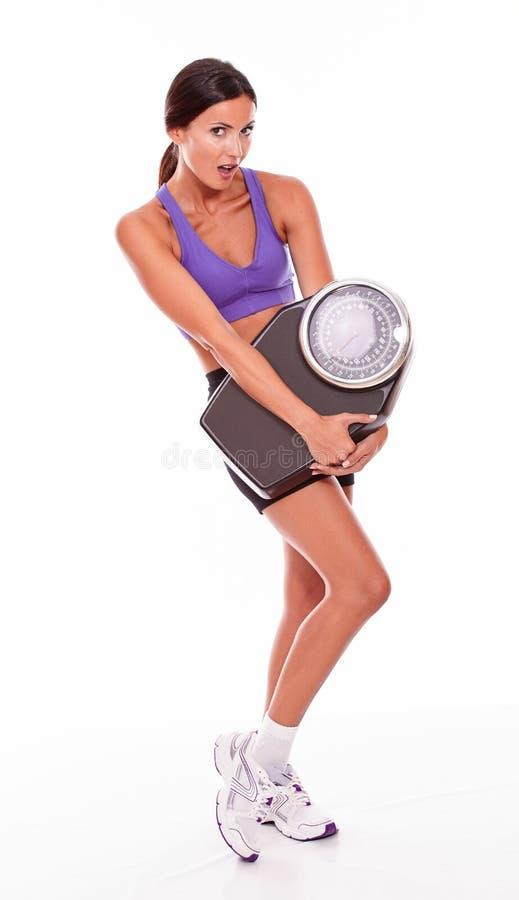拿着标度的健康深色的妇女 免版税库存图片