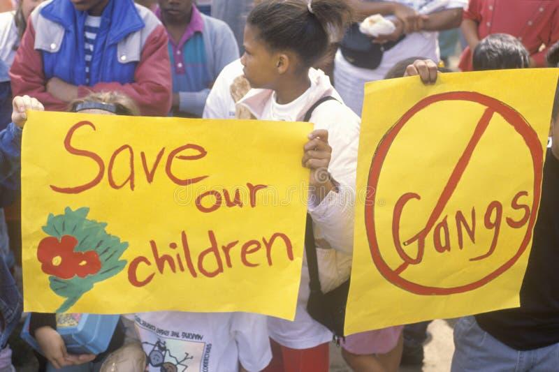 拿着标志的孩子在反帮会社区行军,东部洛杉矶,加利福尼亚 库存图片