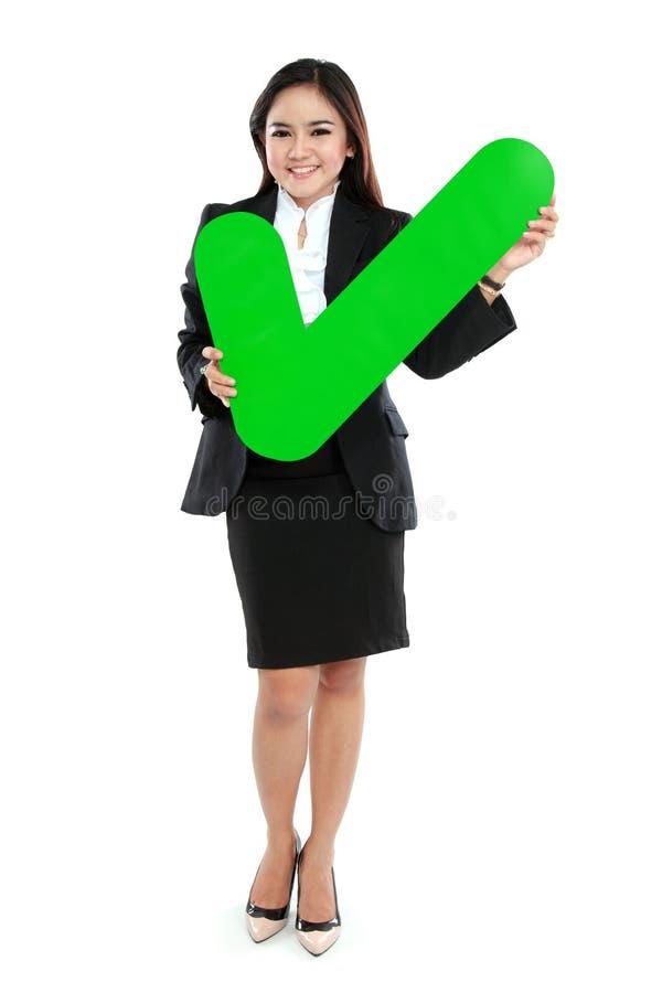 拿着校验标志标志的全长女实业家 免版税库存照片