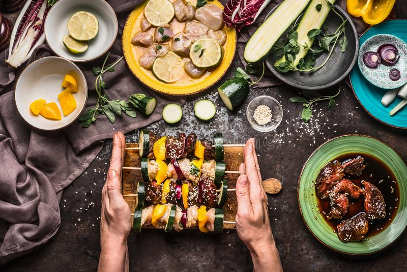 拿着格栅或bbq的女性手各种各样的自创肉菜串在与成份,板材的土气背景和 免版税库存照片