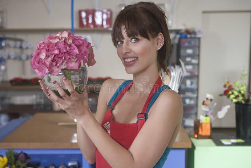 拿着桃红色八仙花属的愉快的卖花人 免版税库存图片