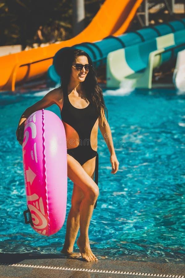 拿着桃红色可膨胀的圆环的妇女在与幻灯片的水池附近 免版税图库摄影