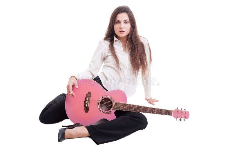 拿着桃红色吉他的性感的年轻和美丽的女性或妇女 库存照片