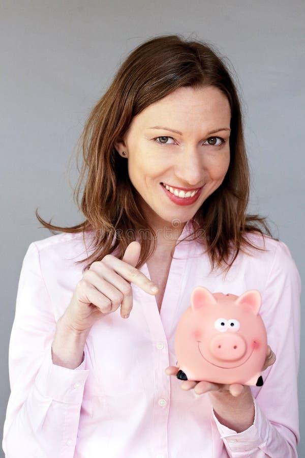 拿着桃红色存钱罐moneybox的金钱储款确信的妇女 库存图片