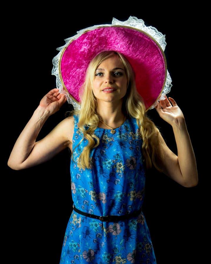拿着桃红色帽子的蓝色礼服的俏丽的妇女 免版税库存照片