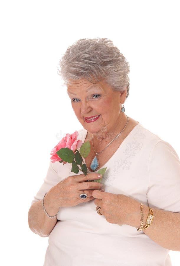拿着桃红色玫瑰的资深妇女 图库摄影