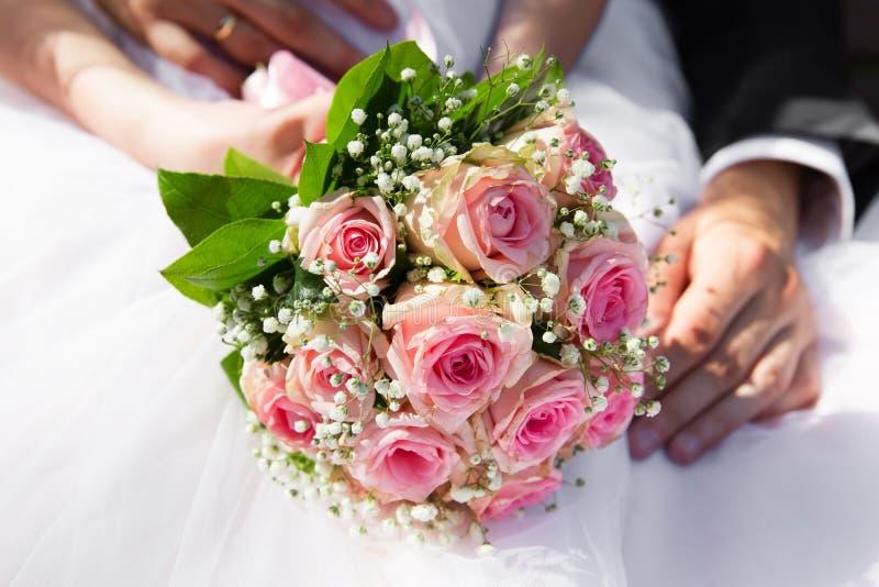 拿着桃红色玫瑰花束的新娘和新郎手 免版税库存照片