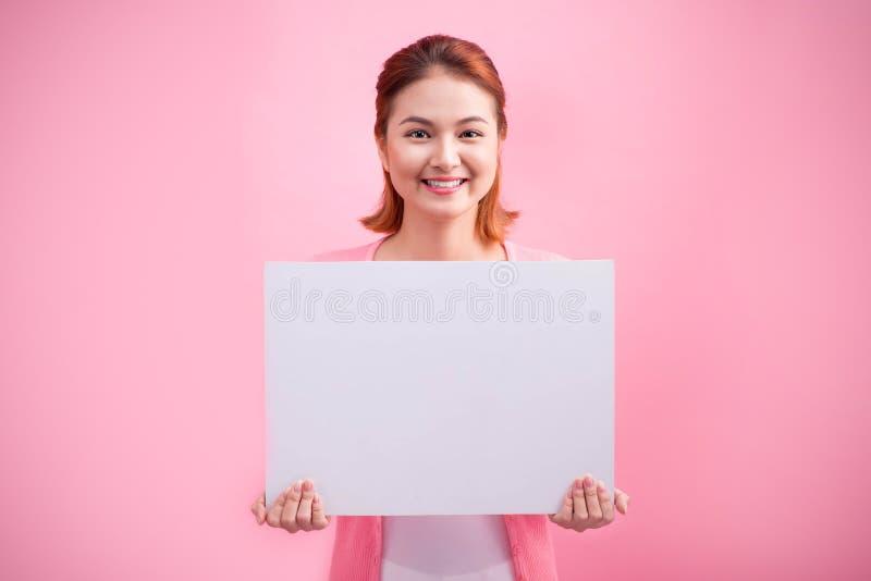 拿着桃红色背景的快乐的美丽的亚裔少妇空白的委员会 图库摄影