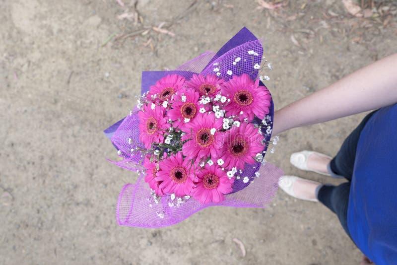 拿着桃红色花的手 库存图片