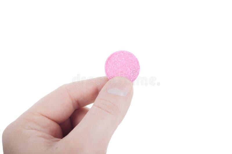 拿着桃红色药片的手指 免版税库存图片