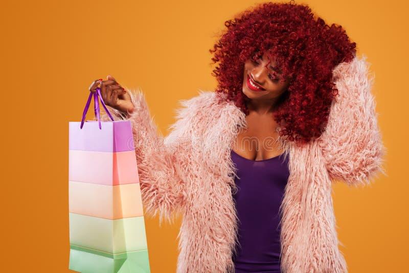 拿着桃红色袋子的购物的美国黑人的妇女被隔绝在橙色背景黑星期五假日 复制空间为 库存照片