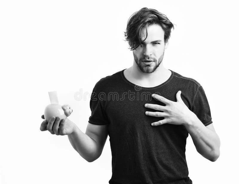 拿着桃红色贪心猪银行的白种人性感的年轻强壮男子 图库摄影