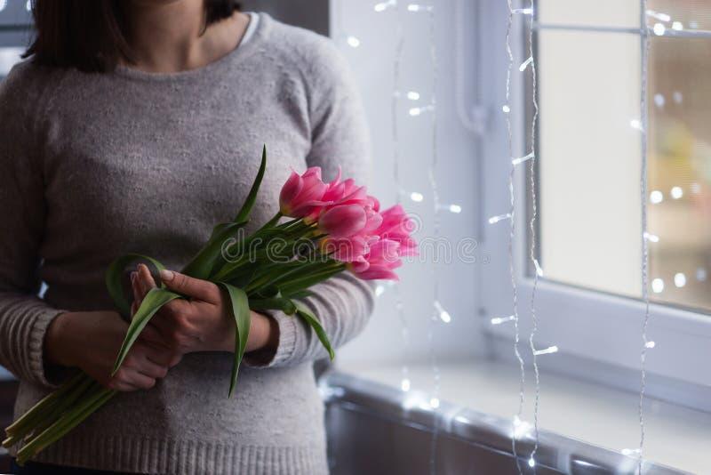 拿着桃红色郁金香的嫩花束年轻女人在与不可思议的bokeh光的窗口附近 图库摄影