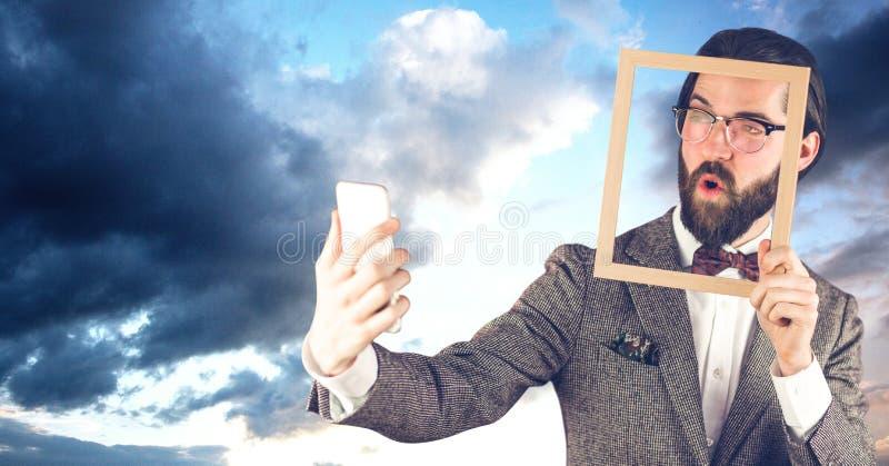 拿着框架的嬉皮商人,当采取在巧妙的电话时的selfie 库存图片