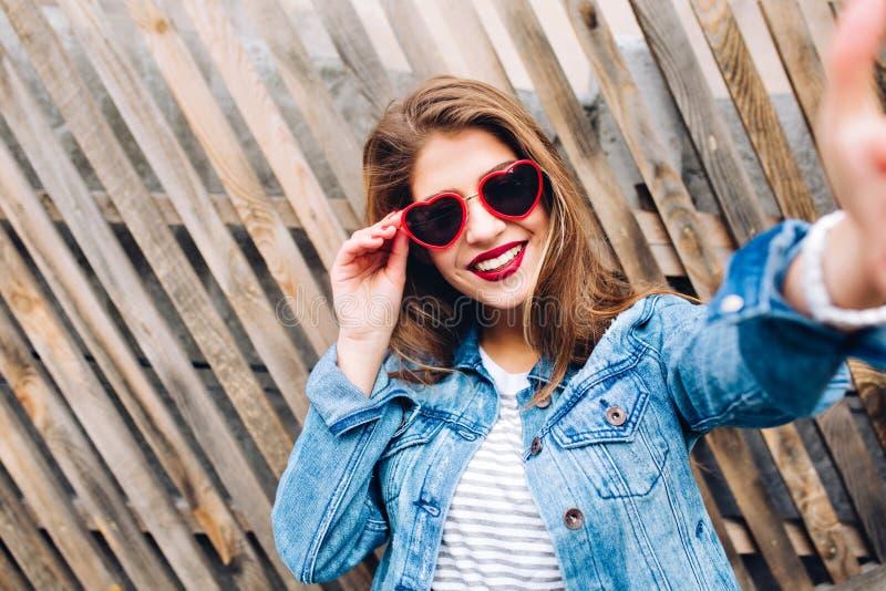 拿着框架的魅力微笑的女孩佩带的心脏玻璃 特写镜头画象迷住年轻俏丽妇女接触 免版税库存图片