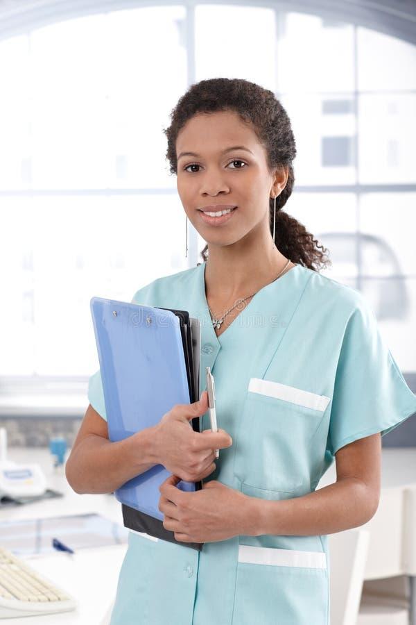 拿着案件页的可爱的护士 库存照片