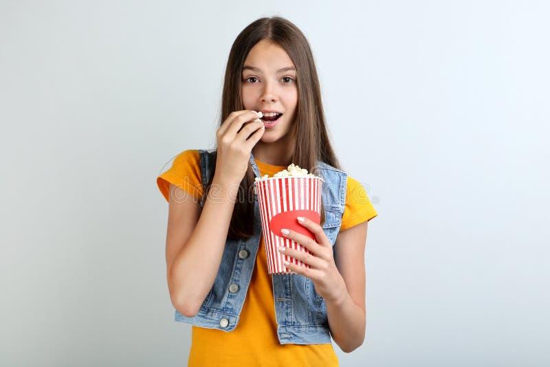 拿着桶用玉米花的女孩 免版税库存图片