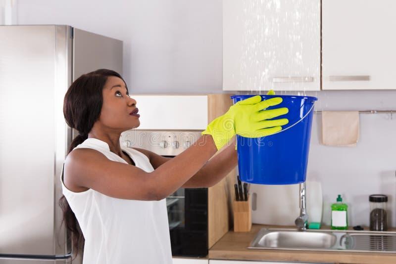 拿着桶的妇女,当水滴从天花板时漏 库存图片