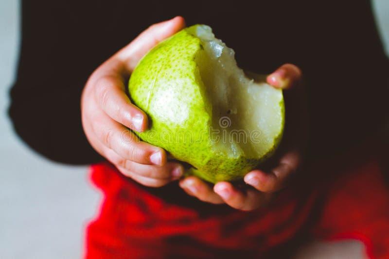 拿着梨的男孩 免版税库存图片